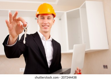 civil engineer with a laptop gives the keys to the apartment