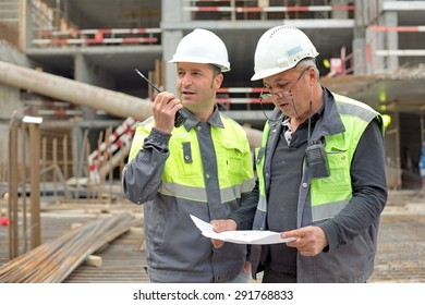 Civil Engineer and Senior Brigadier At Construction Site are inspecting ongoing production according to design drawing.