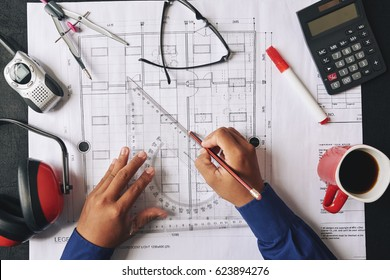 Civil engineer using triangle to draw house plan, view from the top