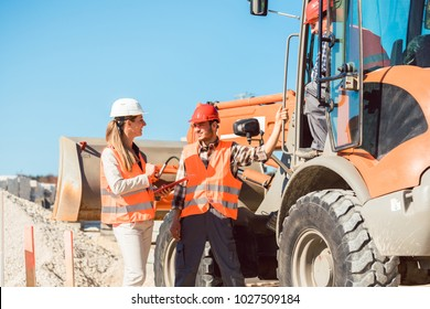 Civil engineer and worker discussion on road construction site, woman and man