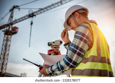 Civil Engineering, Surveyor people making on construction site and holding blueprint in his hand for checking with surveying telescope instrument