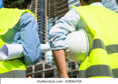 Civil engineers or architects visiting construction site, carrying plan and helmet