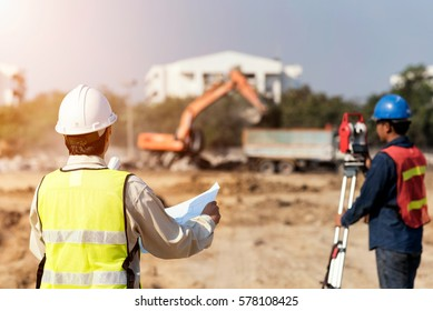 Civil Engineers At Construction Site and A land surveyor using an altometer