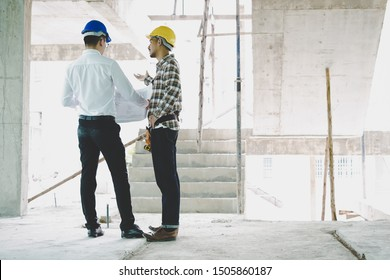 Civil engineers discussing about project with blueprint in construction site. Engineering concept.
