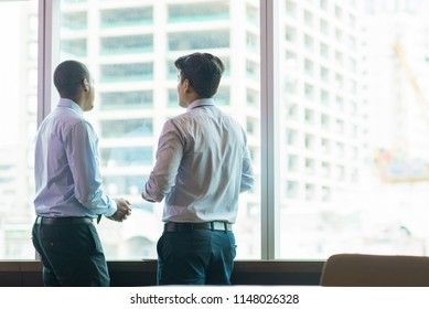 Civil engineers discussing ongoing project. Back view of two business experts looking out office window and reviewing construction progress. Real estate development concept