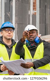 Civil engineers with hardhat and yellow jacket checking technical drawings and office blueprints among scaffolding on construction site