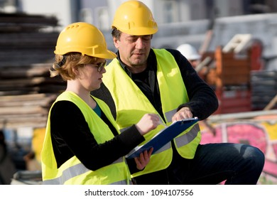 Civil engineers, a man and a woman, wearing safety jackets and helmets, checking projects on construction site