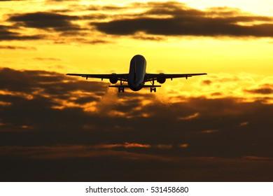 Civil passenger airplane departing during sunset.