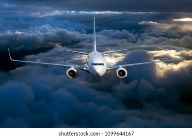 Civil passenger plane in flight. Aircraft flying on a high altitude above the storm clouds during sunset.