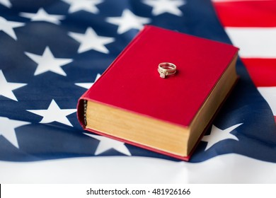 civil rights, family values and marriage concept - close up of american flag and wedding rings on book or bible