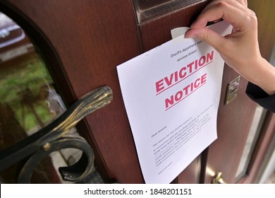 Civil servant sticks a notice of eviction of the tenant, close up