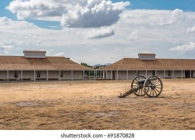 Civil war canon sitting in the courtyard of Fort Davis military post with barracks in the background