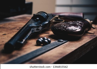 Civil War style 1860 cap and ball black powder revolver replica with brass powder flask on wooden surface with 5 lead ball projectiles