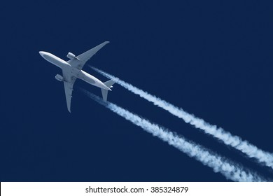 Civil wide-body airliner flying on a high altitude with condensation trail forming behind.