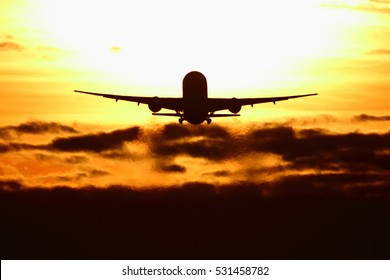 Civil wide-body passenger airplane departing during sunset.