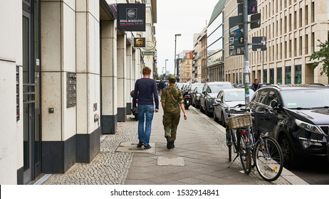 Civilian dressed male and female in camouflage military uniform walk together down a typical busy European urban street in Berlin, Germany.  August 2019