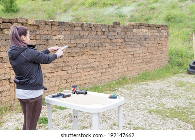 Civilian girl is practicing with her 9mm gun in a shooting range for improving her self-defense technique with gun