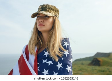 civilian woman in her husband's military cap. A widow with a flag of the united states left without her husband. Memorial Day to fallen soldiers in the war. May 27th is a memorial day.