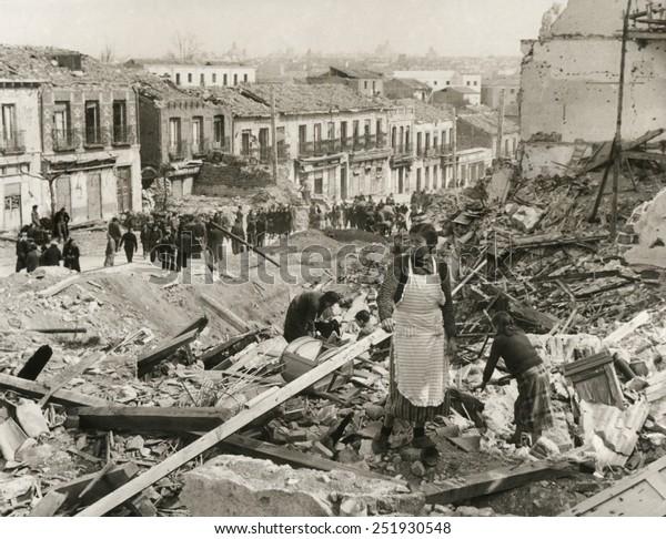 """Civiles en Madrid buscan entre los escombros de sus casas en el """"Madrid Liberado"""". Los nacionalistas finalmente capturaron la asediada ciudad el 28 de marzo de 1939. Guerra Civil Española, julio 1936-marzo 1939."""