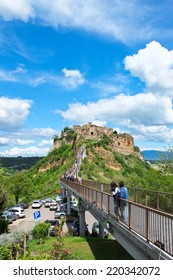 CIVITA DI BAGNOREGIO, ITALY - MAY 1 2013: The long bridge of city, crowded with tourists during festive days.