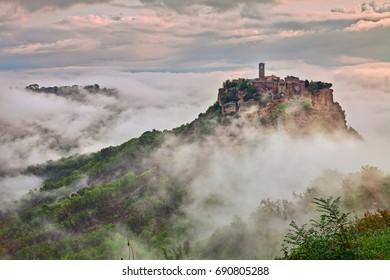 Civita di Bagnoregio, Viterbo, Lazio, Italy: picturesque landscape at dawn of the ancient village shrouded in fog on the steep tuff hill