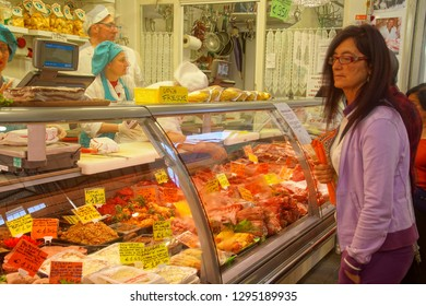 CIVITAVECCHIA, ITALY - APR 21, 2018 - Worker at a meat counter at the central Market in Civitavecchia, Italy