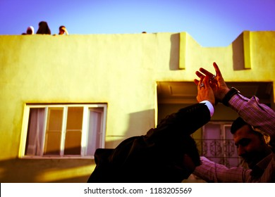 Cizre, Kurdistan / Turkey - June 3, 2012: Men are dancing on the wedding while woman with kids observing from roof. Daily life of people before the military conflict on Turkish-Syrian-Iraqi tripoint
