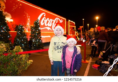 Clacton on Sea, Essex - 20th December 2017 - A brother and sister pose with the world famous Coca Cola, CocaCola Christmas truck, lorry on view for all to see