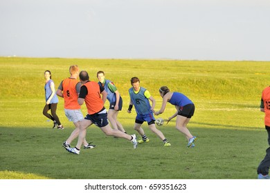 Claddagh, Galway, Ireland june 2017, friends playing touch rugby  in the free public south park fields, a girl executing a pass.