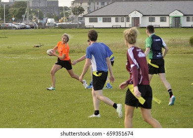 Claddagh, Galway, Ireland june 2017, friends playing touch rugby  in the free public south park fields, a girl is running with the ball while a player from the other team almost get her strip.