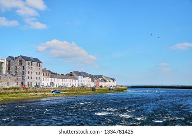 The Claddagh Galway in Galway, Ireland. People sitting at shore enjoying sunny summer day.