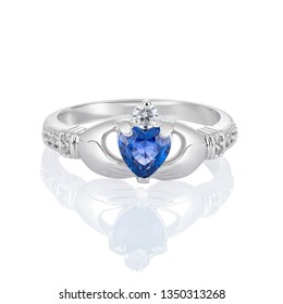 Claddagh ring with blue topaz isolated on white. Traditional Irish ring in shape of two hands holding a heart shaped blue gemstone which represents love, loyalty, and friendship