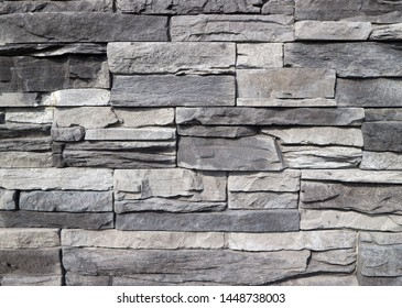 Cladding wall made of  stacked  rough natural stones. Colors are shades of gray. Background and texture.