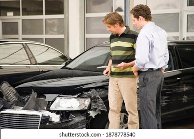 A claims adjuster showing the owner the damage done to the car after his assessment. He is holding a clipboard in his hand.