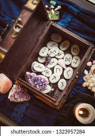 Clairvoyant tools rune stones, crystal pendulums in natural dark wooden case box on dark blue background.