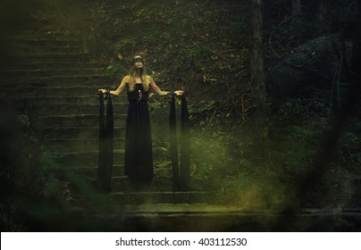Clairvoyant. Woman with black ribbon tied in mystical and mysterious forest