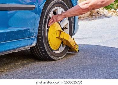 Clamped front wheel of illegally parked car, yellow clamp attached to wheel