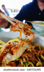 Clamping a crispy pork. Khao soi is a northern food of Thailand.
