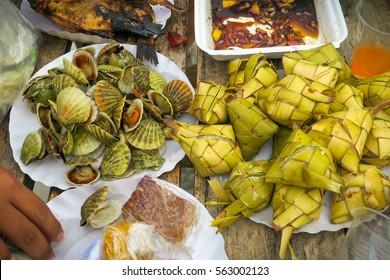 Clams, Fried fish, hanging rice (puso) and bibingka at a Pinoy picnic on the beach