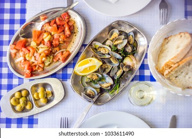 Clams served on silverware, white wine, tomato salad, bread and olives, Portugal