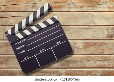 Clap board on wooden background top view