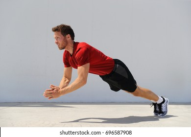 Clap pushup fitness man doing plyometrics push-up exercises explosive workout for muscles training. Athlete working out on gym floor outdoor.
