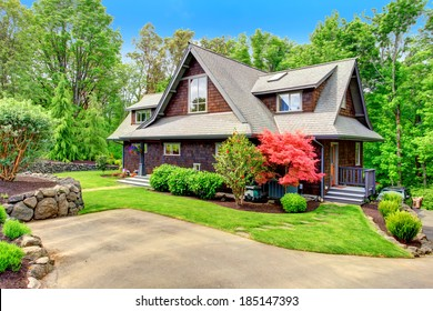 Clapboard siding brown house with green lawn and amazing blooming trees. View from the driveway