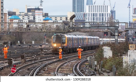 Clapham Junction, London, UK; 10th February 2019; Three Railway Workers Walk Along Tracks With a Train Behind