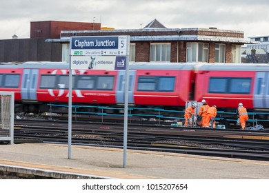 Clapham Junction, London, UK; 1st February 2018; Group of Rail Workers with Train Speeding Past