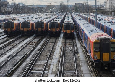 Clapham Junction Railway Station, London - March 8 2018: commuter trains stand in sidings in the train yard. A single train leaves its siding.