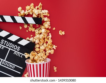 Clapper board with popcorn against red background,Cinema minimal concept,top,view