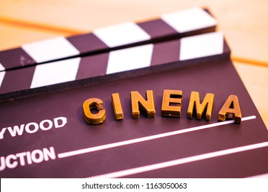 "clapperboard with caracter ""cinema"" on wooden background"