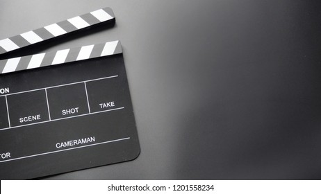 Clapperboard or clap board or movie slate with hands opening board.It's use in video production , film, cinema industry. It's black color on black background.
