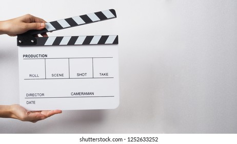 Clapperboard or clap board or movie slate with hands opening board.It's use in video production , film, cinema industry. White color on white background.